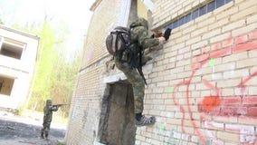军服的Airsoft人有武器的爬上被破坏的房子 股票视频
