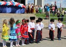 军校学生和女孩执行哥萨克舞蹈 免版税图库摄影
