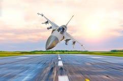 军用喷气式歼击机高速飞行在滑行道在机场 免版税库存照片
