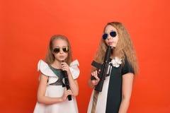 军用礼服的两个女孩有胳膊在手中和太阳镜的o 免版税库存图片