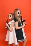 军用礼服的两个女孩有胳膊在手中和太阳镜的o 免版税库存照片