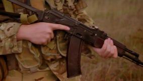 军用自动炮特写镜头射击在被伪装的战士的手上,走在被隔绝的高草,天空蔚蓝 影视素材