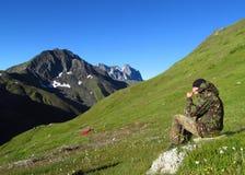 军用衣裳的人在山绿色山谷 库存图片