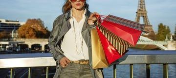 军用防水短大衣的时髦妇女有购物袋的在巴黎,法国 库存图片