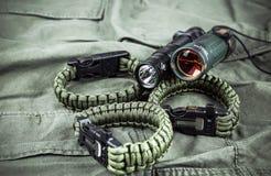 军用paracord镯子、作战火炬和小望远镜 免版税库存图片