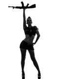 军队一致的向致敬的kalachnikov剪影的性感的妇女 免版税库存照片