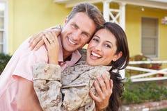 军队事假的丈夫欢迎妻子家 免版税库存图片