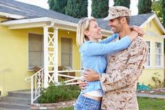 军队事假的妻子欢迎丈夫家 库存照片