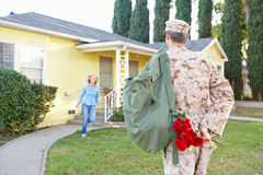 军队事假的妻子欢迎丈夫家 免版税库存照片