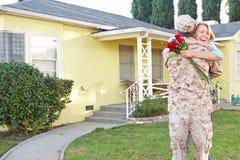 军队事假的妻子欢迎丈夫家 免版税库存图片