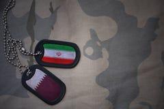 军队空白、卡箍标记与伊朗的旗子和卡塔尔卡其色的纹理背景的 免版税库存图片