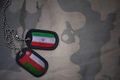 军队空白、卡箍标记与伊朗的旗子和阿曼卡其色的纹理背景的 免版税库存图片