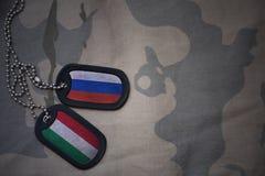 军队空白、卡箍标记与俄罗斯的旗子和匈牙利卡其色的纹理背景的 库存图片