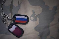 军队空白、卡箍标记与俄罗斯的旗子和卡塔尔卡其色的纹理背景的 免版税图库摄影