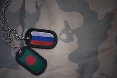 军队空白、卡箍标记与俄罗斯的旗子和孟加拉国卡其色的纹理背景的 库存照片