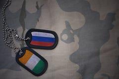 军队空白、卡箍标记与俄罗斯的旗子和棚divoire在卡其色的纹理背景 库存图片