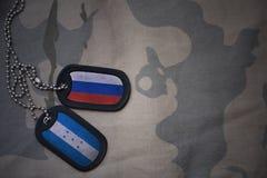 军队空白、卡箍标记与俄罗斯的旗子和洪都拉斯卡其色的纹理背景的 免版税库存照片