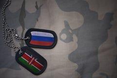 军队空白、卡箍标记与俄罗斯的旗子和肯尼亚卡其色的纹理背景的 库存照片