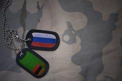 军队空白、卡箍标记与俄罗斯的旗子和赞比亚卡其色的纹理背景的 免版税库存图片