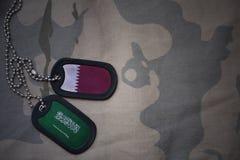 军队空白、卡箍标记与卡塔尔的旗子和沙特阿拉伯卡其色的纹理背景的 库存图片