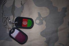 军队空白、卡箍标记与卡塔尔的旗子和阿富汗卡其色的纹理背景的 库存照片