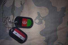 军队空白、卡箍标记与叙利亚的旗子和阿富汗卡其色的纹理背景的 库存照片