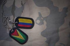 军队空白、卡箍标记与哥伦比亚的旗子和圭亚那卡其色的纹理背景的 图库摄影