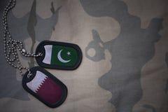 军队空白、卡箍标记与巴基斯坦的旗子和卡塔尔卡其色的纹理背景的 图库摄影