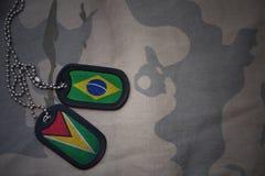 军队空白、卡箍标记与巴西的旗子和圭亚那卡其色的纹理背景的 库存照片