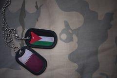 军队空白、卡箍标记与约旦的旗子和卡塔尔卡其色的纹理背景的 免版税库存图片