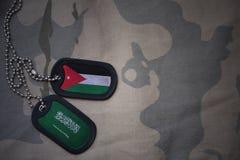 军队空白、卡箍标记与约旦的旗子和沙特阿拉伯卡其色的纹理背景的 库存照片