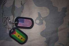 军队空白、卡箍标记与美国的旗子和圣多美岛和普林西比岛卡其色的纹理背景的 库存照片