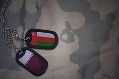军队空白、卡箍标记与阿曼的旗子和卡塔尔卡其色的纹理背景的 库存照片