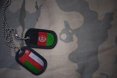 军队空白、卡箍标记与阿曼的旗子和阿富汗卡其色的纹理背景的 免版税库存图片