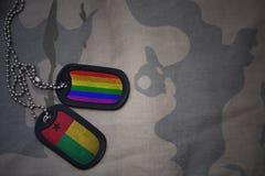 军队空白,与几内亚比绍的旗子和快乐彩虹旗子的卡箍标记在卡其色的纹理背景 库存图片
