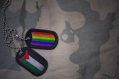 军队空白,与巴勒斯坦的旗子和快乐彩虹旗子的卡箍标记在卡其色的纹理背景 库存图片