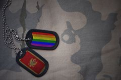 军队空白,与黑山的旗子和快乐彩虹旗子的卡箍标记在卡其色的纹理背景 库存照片