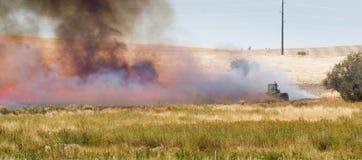 农业农夫烧伤植物偷偷靠近收获火拖拉机 免版税库存照片