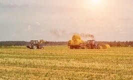 农业和拖拉机收集在农厂植物的秸杆大包 免版税库存照片
