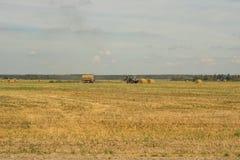 农业和拖拉机收集在农厂植物的秸杆大包 免版税图库摄影