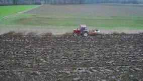 农业和种田-在早期的春天的拖拉机鸟瞰图耕一个领域 股票视频