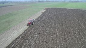 农业和种田-在早期的春天的拖拉机鸟瞰图耕一个领域 影视素材