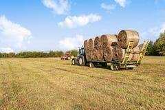 农业场面 在手推车的拖拉机增强的干草捆 库存图片