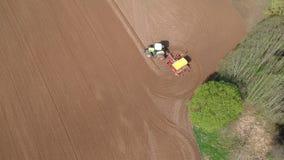 农业拖拉机在春天领域的播种庄稼在树丛附近,空中 股票录像