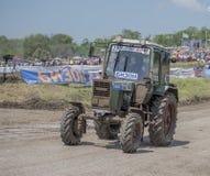 农业拖拉机的竞争在绿色草甸 库存照片