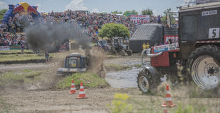 农业拖拉机的竞争在绿色草甸 库存图片