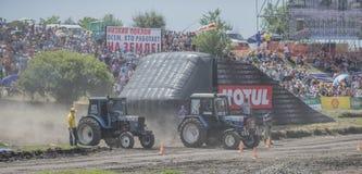 农业拖拉机的竞争在绿色草甸 免版税库存照片