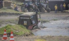 农业拖拉机的竞争在绿色草甸 免版税库存图片