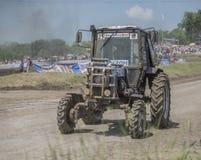 农业拖拉机的竞争在绿色草甸 图库摄影