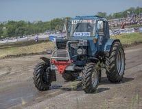 农业拖拉机的竞争在绿色草甸 Bizo 库存图片